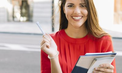 portrait-of-a-happy-young-woman-holding-diary_23-2147925273