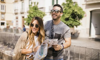 smiling-young-couple-standing-on-street-holding-map_23-2147841645